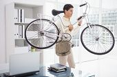 Handsome businessman carrying his bicycle in his office