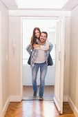 Cute couple walking through the door in their new home