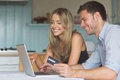 Cute couple using laptop together to shop online at home in the kitchen