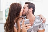 Young man using smartphone while girlfriend kisses him at home in the kitchen
