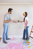 Cute couple painting the wall in their new home