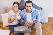 Cute couple sitting on floor using laptop in their new home
