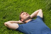 Casual man lying on the grass at home in the garden