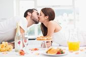 Young couple having a romantic breakfast at home in the kitchen
