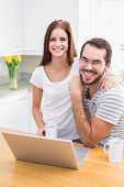 Young couple smiling at the camera using laptop at home in the kitchen