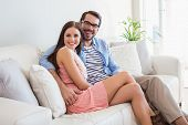 Young couple smiling at camera on couch at home in the living room