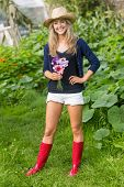 Pretty blonde smiling at camera holding flowers at home in the garden