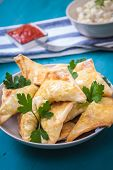 stock photo of samosa  - indian samosa filled with chicken curry on tray - JPG