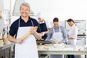 Portrait of happy male chef holding rolling pin while colleagues preparing pasta at commercial kitchen