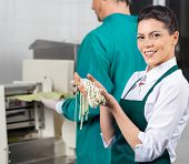 Portrait of happy young female chef holding fresh spaghetti pasta with colleague in background at kitchen