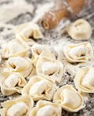 Closeup of flour and raw ravioli pasta on counter in commercial kitchen