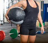 Midsection of fit woman carrying medicine ball in gym