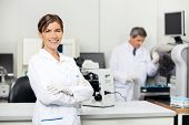Smiling mid adult female scientist with colleague working in background at medical laboratory
