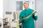 Portrait of confident male chef in protective workwear holding green spaghetti pasta sheet by machine at commercial kitchen