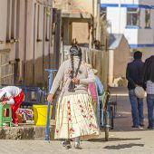 COPACABANA, BOLIVIA, MAY 6, 2014:  Local woman in traditional costume walks down the street