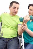 stock photo of physical therapist  - Physical therapist works with patient in lifting hands weights - JPG