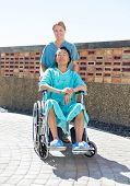 Portrait of confident nurse pushing relaxed patient on wheelchair at courtyard