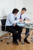 Businessmen discussing paperwork at desk in office