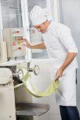 Male chef operating spaghetti pasta machine at commercial kitchen