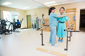 Female physical therapists assisting patients in hospital gym
