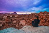 stock photo of goblin  - Girl Hiker looking at changing Colorful Sunset Clouds over the Goblin Valley Utah - JPG