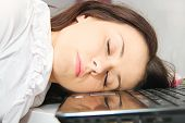 Tired business woman fell asleep next to a laptop