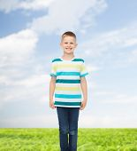 happiness, childhood, environment and people concept - smiling little boy in casual clothes with crossed arms over natural background