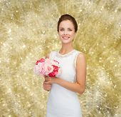 people, wedding, holidays and celebration concept - smiling bride or bridesmaid in white dress with bouquet of flowers over yellow lights background