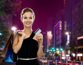 people, sale, christmas and holidays concept - smiling elegant woman in evening dress with shopping bags and credit card over night city background