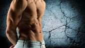 sport, bodybuilding, strength and people concept - close up of male bodybuilder bare torso over concrete wall background