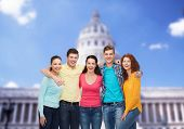friendship, tourism, travel and people concept - group of smiling teenagers standing over white house background