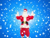 christmas, holidays and people concept - man in costume of santa claus having fun over blue snowy background
