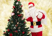 christmas, holidays and people concept - man in costume of santa claus with bag and christmas tree waving hand over yellow lights background