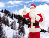 christmas, holidays, gesture and people concept - man in costume of santa claus with bag waving hand over snowy mountains
