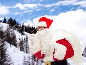 christmas, holidays and people concept - man in costume of santa claus with bag pointing finger over snowy mountains