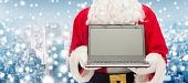 christmas, advertisement, technology, and people concept - close up of santa claus with laptop computer over snowy city background