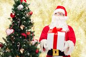 christmas, holidays and people concept - man in costume of santa claus with gift box and tree over yellow lights background