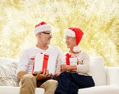 family, holidays, christmas, age and people concept - happy senior couple in santa helper hats with gift boxes over yellow background