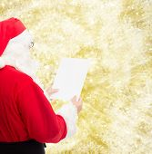 christmas, holidays and people concept - man in costume of santa claus reading letter over yellow lights background