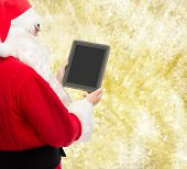 christmas, advertisement, technology, and people concept - man in costume of santa claus with tablet pc computer over yellow lights background