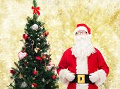 holidays and people concept concept - man in costume of santa claus with christmas tree over yellow lights background