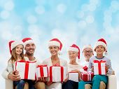 family, happiness, generation, holidays and people concept - happy family in santa helper hats with gift boxes sitting on couch over blue lights background