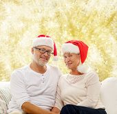 family, holidays, christmas, age and people concept - happy senior couple in santa helper hats sitting on sofa over yellow lights background