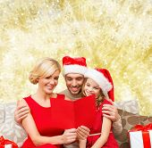 christmas, holidays, family and people concept - happy mother, father and little girl in santa helper hats with gift boxes reading geeting card over yellow lights background