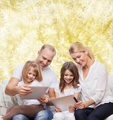 family, holidays, technology and people - smiling mother, father and little girls with tablet pc computers over yellow lights background