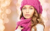 happiness, winter holidays, christmas and people concept - close up of young woman in pink hat and scarf over beige lights background