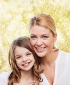 family, childhood, happiness and people - smiling mother and little girl over yellow lights background