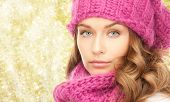 happiness, winter holidays, christmas and people concept - close up of young woman in pink hat and scarf over yellow lights background
