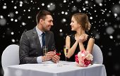 celebration, christmas, holidays and people concept - smiling couple with red gift box and ring at restaurant over black snowy background