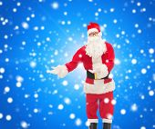 christmas, holidays, gesture and people concept - man in costume of santa claus over blue snowy background